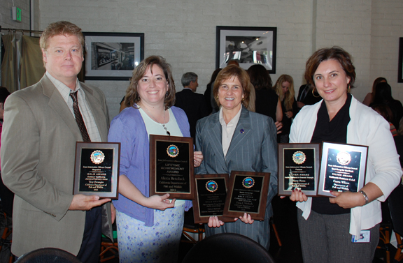 one man and three women holding award plaques
