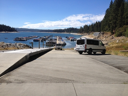 concrete boat-launching ramp leads into a blue lake with small docks