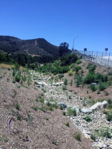 A dry streambed full of rocks next to a chain link fence alongside a rural southern Calfiornia freeway