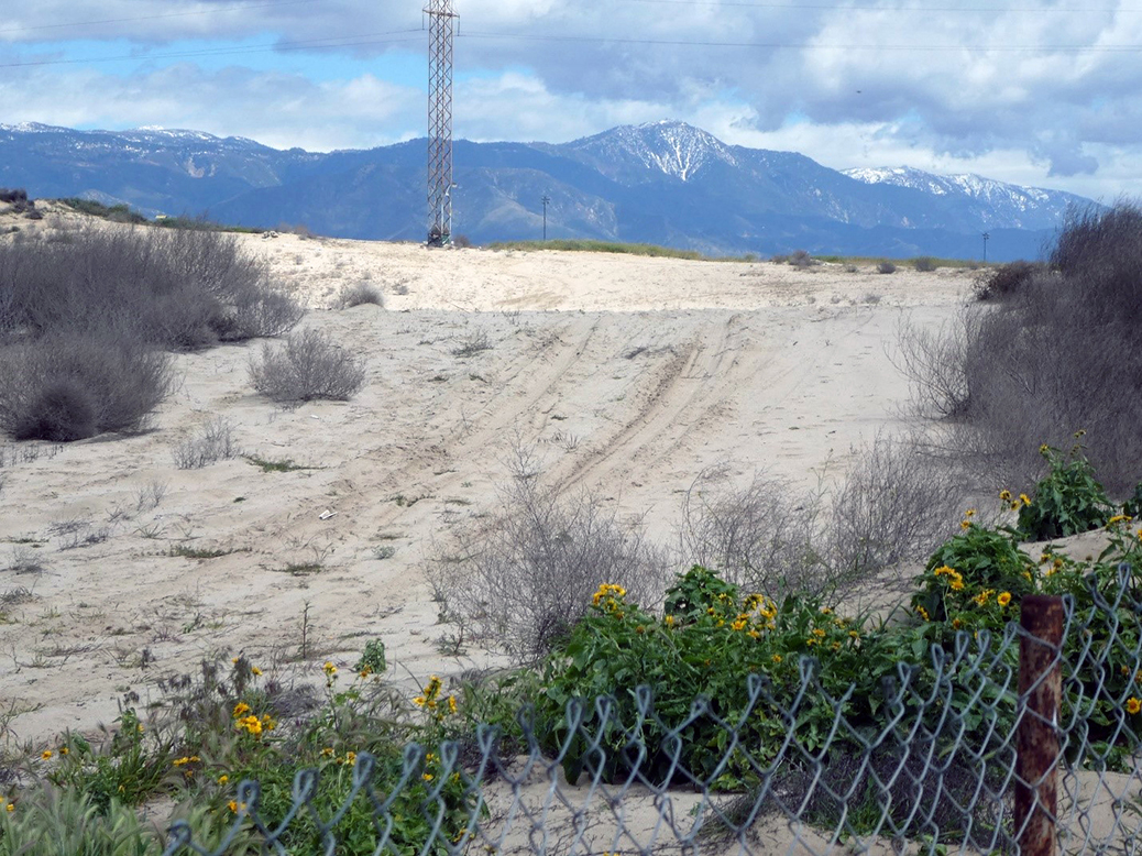 Sand dune, damaged by off-road vehicles, behind a chain-link fence, with snow-capped mountains under a cloudy sky in background