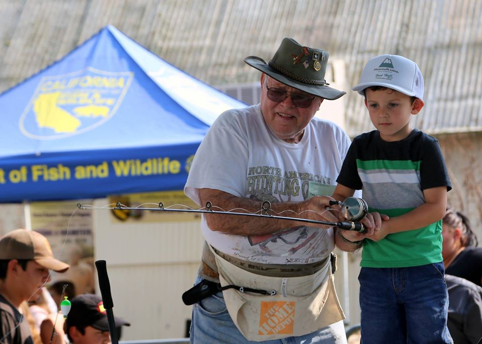 Adult volunteer helping a child learn to fish at Fred Hall Show