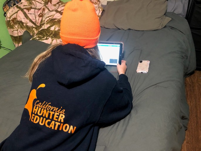 girl wearing Hunter Education sweatshirt studying mobile device