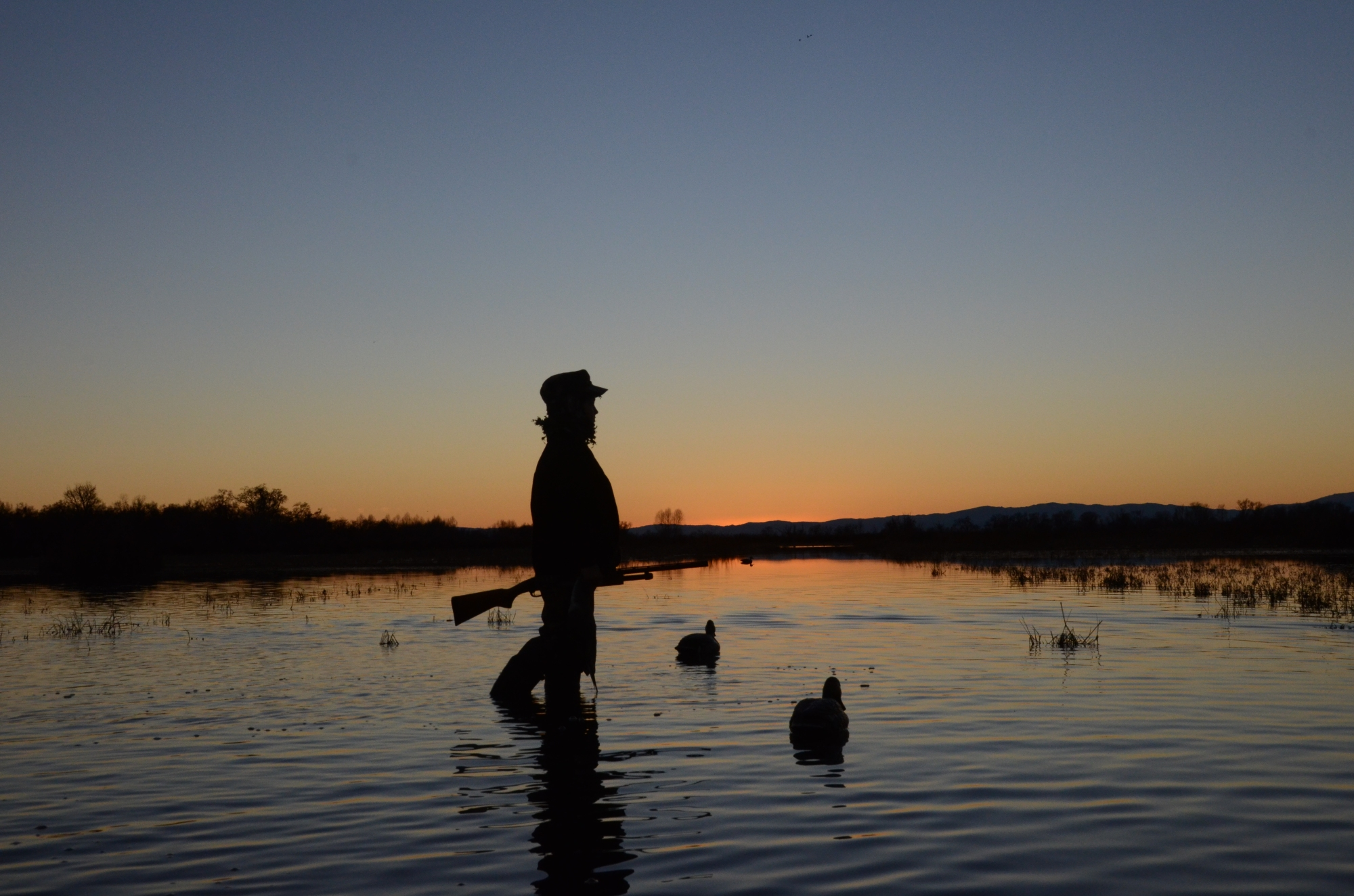Boy with decoys at sunrise